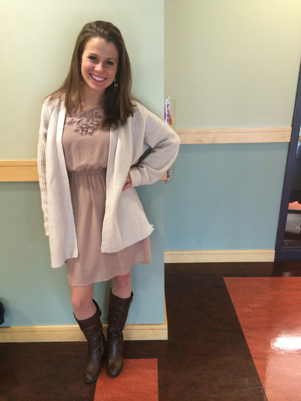 Senior Heather Quirk uses simple neutral colors, a cardigan, and boots to fashionably keep warm in a dress during winter.